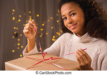 Young woman unwraping a present