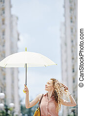 Young woman walking with parasol