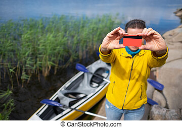 Young woman with a credit card showing lake and kayak.