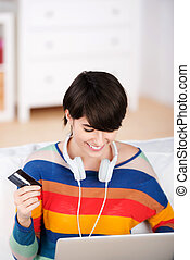 Young woman with a laptop and credit card