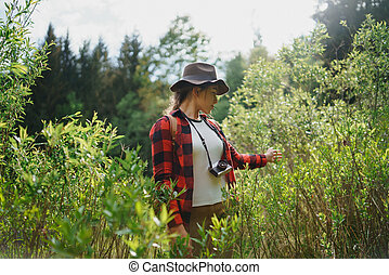 Young woman with camera on a walk in forest in summer nature.