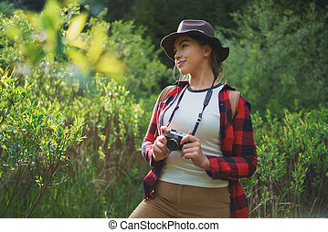 Young woman with camera on a walk in forest in summer nature, standing.