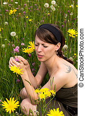 young woman with hayfever in a wildflower meadow
