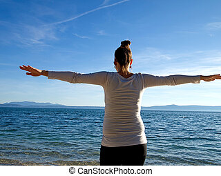 Young woman with open arms on beach