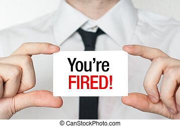 Business man holding a card with you're fired text